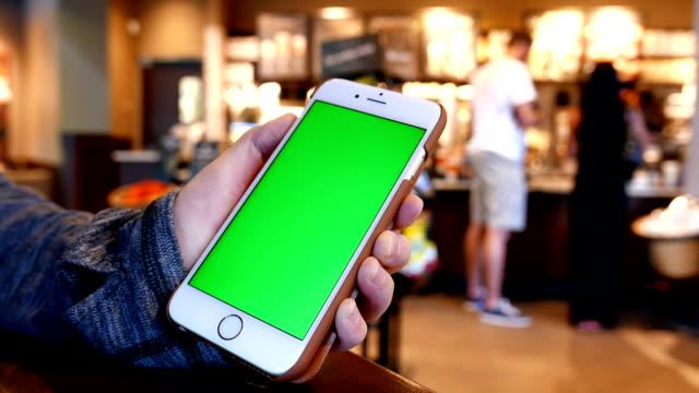 Hand holding green screen iphone inside Starbucks store video