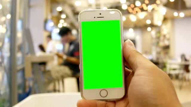 Hand holding smartphone using application of famous social network in Coffee Shop video