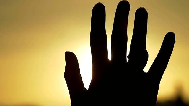 Hand in silhouette raised up to the sun video
