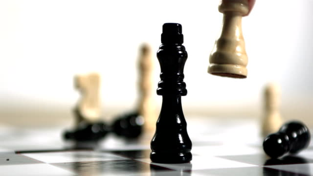 Hand knocking over black chess piece with white one video