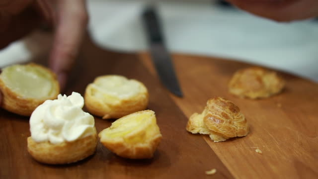Hand making filling chuox cream puff and arranging for sell in bakery shop video