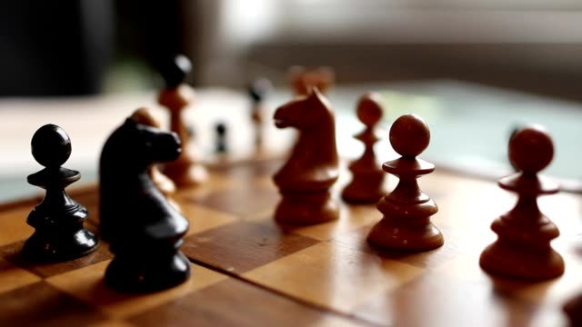 Hand moves chess horse figure in wooden board video
