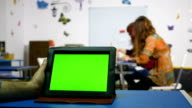 Hand of a man holding tablet pc with green screen in a course room video