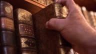 DS Hand of senior man taking old book from shelf video