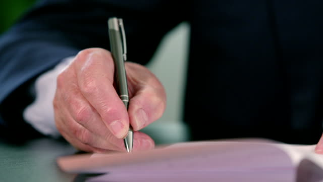 Hand of an old business man signing documents with his pen video