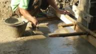 hand of builder worker plastering at floor cement. video