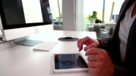 Hand of business man swiping tablet in office video