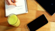 Hand of businesswoman writing on notebook at desk with glass of juice and mobile phone on table video