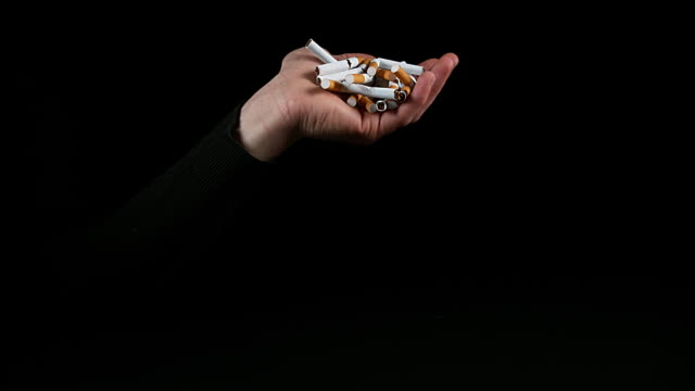Hand of Man and Broken Cigarettes on Black Background, Slow Motion 4K video