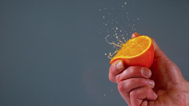Hand of Man Squeezing Orange against Black Background, Slow Motion 4K video