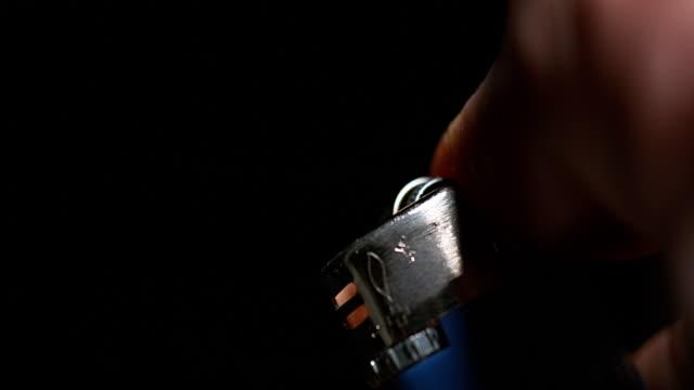 Hand of Man who Lights a Lighter on Black Background, Slow Motion 4K video