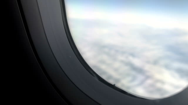 Hand of passenger opening window shade before landing, flight safety measures video