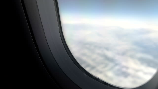 Hand of plane passenger shutting window shade to have rest during long flight video