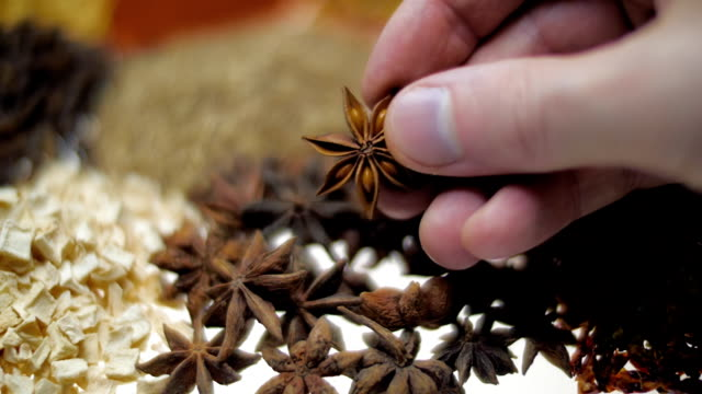 Hand of the cook take anise star-shaped during cooking and looking it. Macro video
