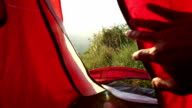 Hand opens up tent flap to peer outside into meadow, sunrise video