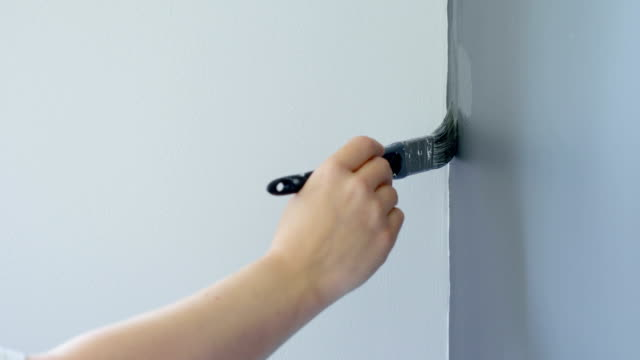 Hand painting the edge of a gray wall with brush video