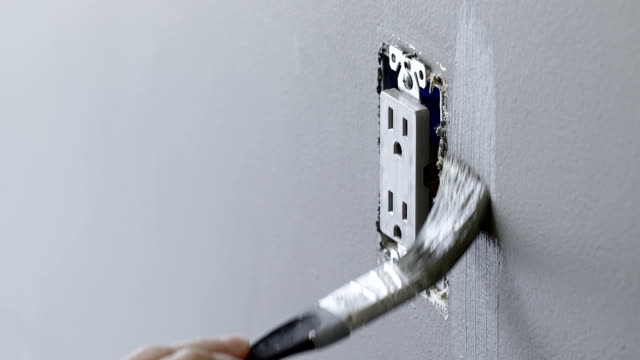 Hand paints around an electrical outlet with brush video