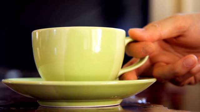 hand picking green cup of coffee on wooden table video