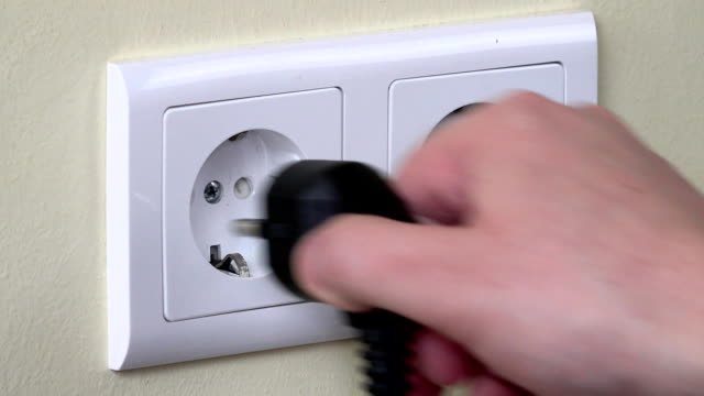 Hand pull out plug wire from outlet and insert child safety plug video