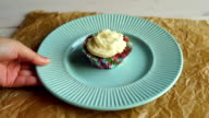 Hand put dessert plate with cupcake on table. Vanilla cupcake with cake cream video