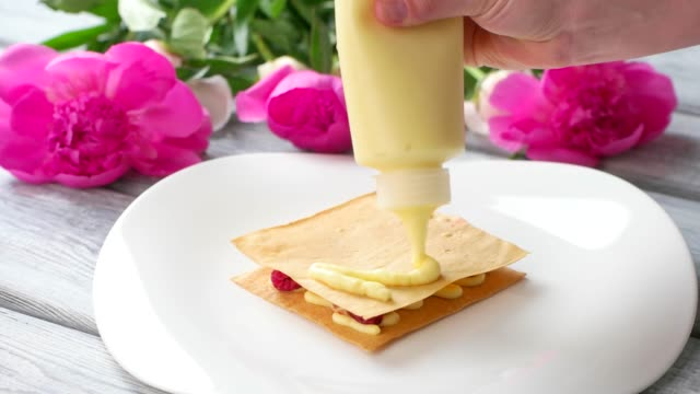 Hand puts cream on shortcake. video