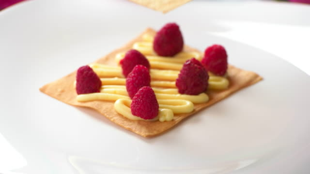 Hand puts shortcake on raspberries. video