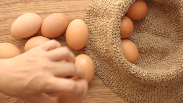 Hand putting egg in brown sack on table video