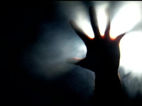 Hand reaching towards foggy light video