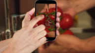 Hand showing cooking clips on smartphone video