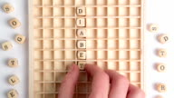 Hand spelling out diabetes message in wooden dice on grid video