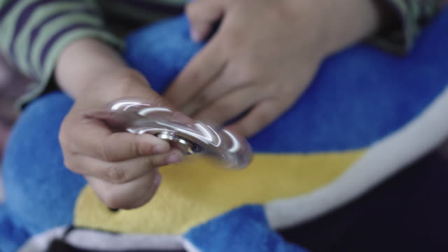 Hand spinner or fidgeting spinner rotating on child's hand (Only the hands) video