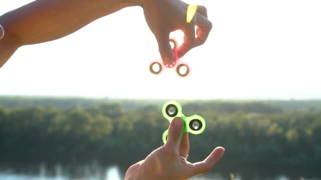 Hand spinner rotating on child's hand, slow motion video