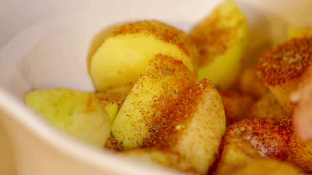Hand sprinkle spices on potatoes. Close up video