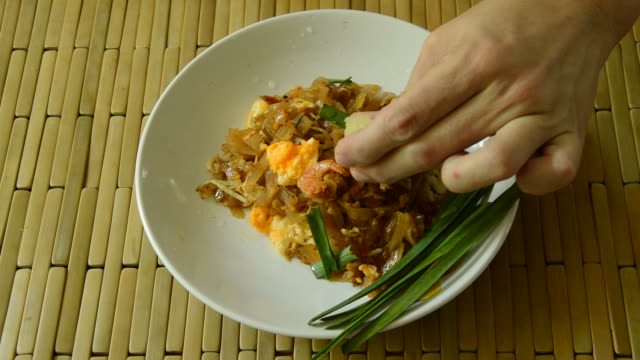 hand squeeze lemon lime on Pad Thai mixed and scooping by fork to eat video