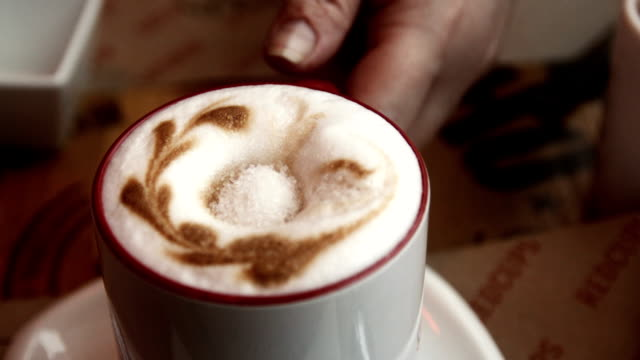 Hand takes a cup of coffee latte video