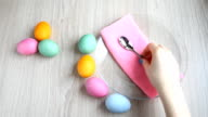 Hand takes a teaspoon from the table. On the table are colored easter eggs. video