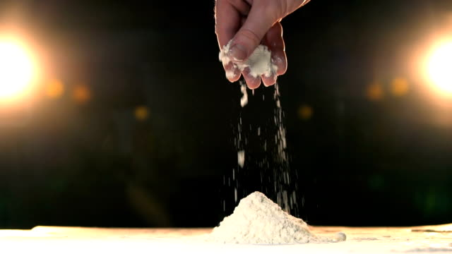 Hand throwing flour in a heap rapid. Hand throws white powder mountain slow mo. video