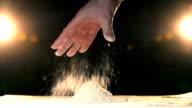 Hand throwing flour in a heap rapid. Hand throws white powder mountain slow mo. video