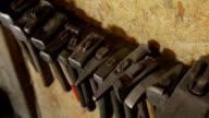 Hand tool for metal forging hangs on wall closeup video