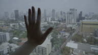 Hand touching glass of window with the cityscape view outside video