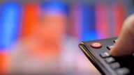 Hand turns on the TV and switch the channels by remote control video