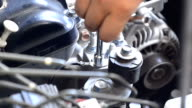 Hand using a wrench to loosen the nut engine grounded of cars video