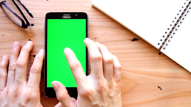hand using mobile phone with green screen on office table - top view video