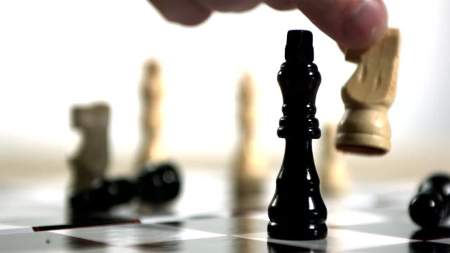 Hand using white knight to knock over king in chess video