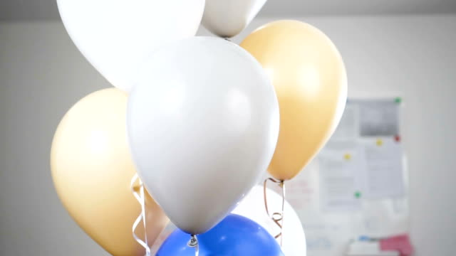 Hand with a knife pierces the balloons and they were blown away and explode. Slow motion. video