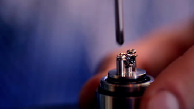 Hand with a screwdriver, unscrews screws holding wire heating element in electronic cigarette video