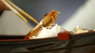 Hand with chopsticks takes shrimp. video