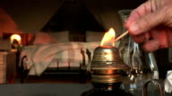 Hand with match lighting old fashioned oil lamp with safari tent in background video