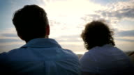 Handheld of two men sitting together watching the sunset video
