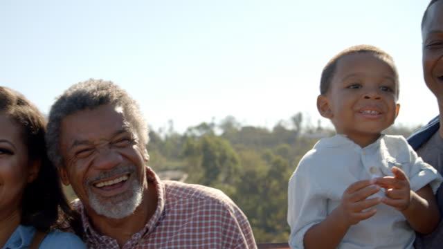 Handheld pan of happy multi generation black family outdoors video